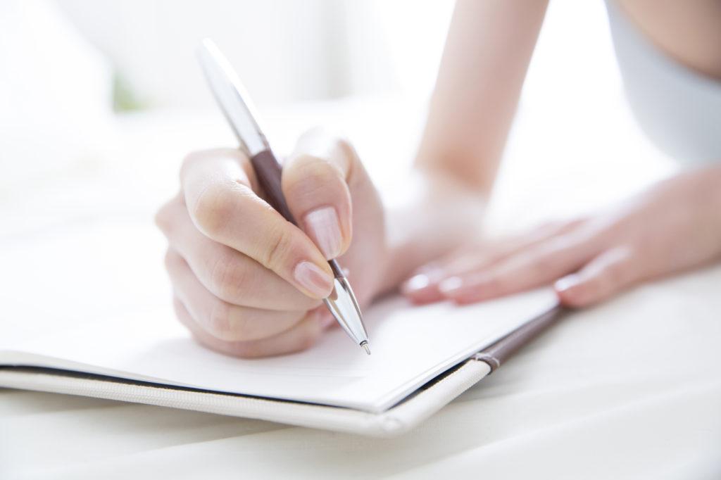 ノートに文字を書く女性