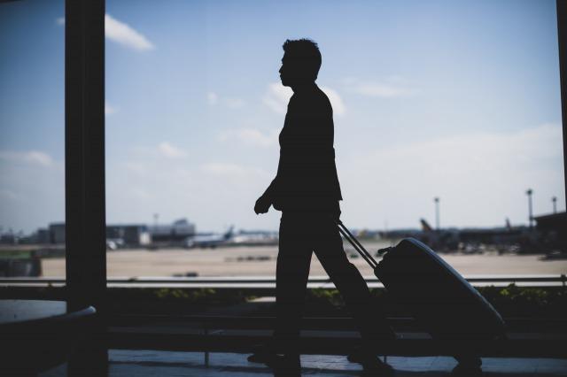 転勤族男性がスーツケースをもって歩いている